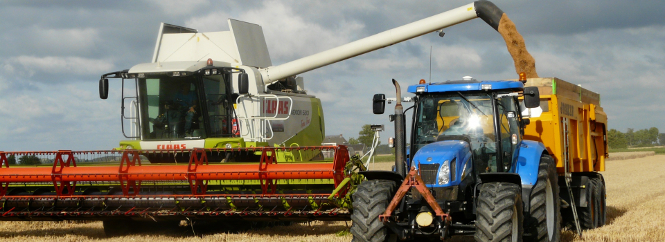 Canva-Blue-Tractor-Next-to-White-Farm-Vehicle-at-Daytime